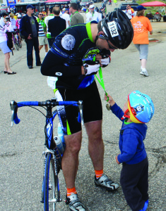 Wheels of Justice Cycling Team Co-captain Aaron Bradford receives a medal from his son at the Courage Classic